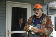 Dennis Ruhnke holds two of his remaining N-95 masks as he stands with his wife, Sharon at their home near Troy Friday, April 24, 2020. Dennis, a retired farmer, shipped one of the couple's five masks left over from his farming days to New York Gov. Andrew Cuomo for use by a doctor or a nurse. (AP Photo/Charlie Riedel)