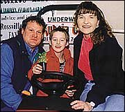 <b>Jonathan Murray, center</b>, and Randy and Kristi Billinger were the first match from Big Brothers/Sisters of Baldwin City. They have been spending a few hours a week together for about a month. On Saturday, they attended a lawn and garden show in Ottawa, because Jonathan likes rocks and Kristi likes flowers. Jonathan also likes tractors, as picture above at the lawn and garden show.