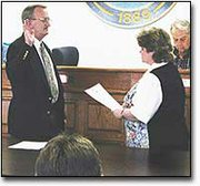 Bill hooker, left, takes the oath of office from City Clerk Mary Mogle to become Basehor's new mayor. Hooker was sworn in Monday night.