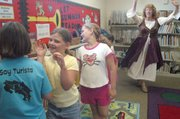 "Young girls playing princesses dance along with storyteller Jo Ho, right, as she actively recounts the brothers Grimm fairy tale, ""The Twelve Dancing Princesses,"" at the De Soto Library Tuesday."