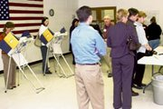 A line of De Soto residents wait their turn to vote Tuesday as others take their turn at three voting machines in the Community Center. At shortly before 5 p.m., workers at the Community Center and De Soto VFW polling places reported 400 people had voted. The De Soto Baptist Church reported 300 on its list had cast ballots with a steady stream still coming to the polls. The turnout in De Soto, where the De Soto USD 232 bond proposal was thought to be unpopular, could have contributed to its narrow defeat. Precinct totals won't be known until next week.