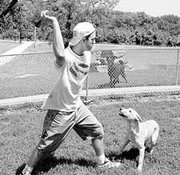 Mike Johnson of Triune Canine Training and Country Resort plays a game of fetch with yellow Labrador Angel. The business features large exercise yards for the dogs staying at the kennel.