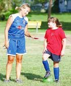 Jen Bertrand instructs camper Suzie Gulley on ball dribbling techniques after a drill. A wide variety of ages of children attended the camp's sessions during the day.