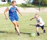 Playing the role of the turnaround monster, Taylor Lowe, 7, blocks the path of Griffiths. In the drill, if a player was caught by the turnaround monster, he or she had to switch directions while dribbling the ball, simulating a game situation when a player is confronted by a defender.