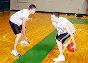 De Soto High School senior basketball players Justin Haub and Toad Twidwell play a game of one-on-one. Despite last season's disappointing 1-15 record, the team hopes a good summer season and weight training will make the difference in 2002.