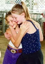 Breanna Sigman, 11, gets a hug from Samantha Brosseau, Olathe, after completing oral judging in the livestock judging competition. The two met and became friends over the course of 4-H events.