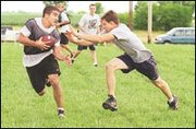 Above, Justin Cobb, a senior at Mill Valley High School, puts a move on his opponent during a seven-on-seven tournament in Eudora Saturday morning.