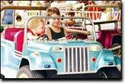Joe (left) and Tony Bukobaz enjoy a ride in a mini-Jeep Saturday at the Watermelon Festival.