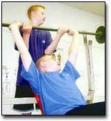 Raymond Wellman spots Josh Turnbaugh as he lifts weights in the Eudora Middle School weight room Tuesday morning. The seventh-grade boys are a part of the school's summer weightlifing program.