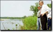 Standing on the bank of the Kansas River, John Pendleton talks with