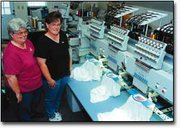 Sherry Coulter and Michelle Weigel keep an eye on Coulter's four-head commercial sewing machine as it embroiders flags on T-shirts.