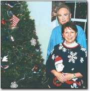 Ginger and Greg Aronhalt divide the holiday decorating chores. He takes care of the decorations outside, and she decorates inside. Here, they stand beside Ginger's patriotic tree which is decked with flags, doves, bells and ribbons.