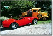 Pete and Irene Tork stand beside two of their vintage vehicles. The 1965 Shelby Cobra replica they built from a kit and the 1934 Ford pickup they completely refurbished prove their mechanical expertise. Irene, a retired nurse, works on the cars alongside her husband. Pete is a retired TWA aircraft mechanic.