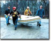 Volunteer members of the county's water rescue team carry their boat to a flooded area in March.