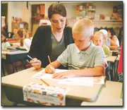 Sam Denholm works on his penmanship with his third-grade teacher, Sara Saunders.