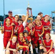 Members of the Tonganoxie Braves softball team celebrate after winning the Field of Dreams Summer Jam Tournament last weekend in Basehor.