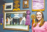 Dozens of Courtenay DeHoff's awards cover a wall in her family's living room.