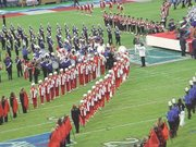 THS band members, dressed in red and white uniforms, perform with Clint Black on the field.