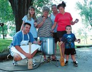 When Tarry Boudreaux and his wife, Jamie, visited the Boudreaux family in Tonganoxie recently, the following family members gathered for a photo, along with the cooker setup in which Jules deep-fat fries gurkeys. From left are Tarry, Jamie, Mary, Jules, Julie and Jordan.