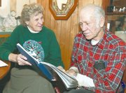 Jody and Fred Chenoweth look at a children's book she wrote about weather. The book includes dozens of cloud pictures that Jody has taken .