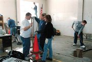 Sherman Township firefighters spent Saturday afternoon cleaning the fire station to ready it for runners who may be stopping by for refreshments Sunday during the Brew to Brew Run. Pictured are T.C. Theno, far left, Mike Gast, fire chief Dan Tallman, Kim Miller and Nicholas Box, 15, who was helping his father, Dale Box. Washing windows is Nikki Briggs.