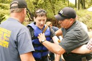 Firefighters assist this boy after he was rescued from Tonganoxie Creek.