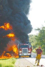 A diesel fuel tanker erupts into a ball of flames as a Lawrence-Douglas County Fire and Medical personnel work to lay out water hoses. The truck carrying 1,700 gallons of diesel fuel exploded on Tuesday east of the intersection of U.S. Highway 24-40 and Kansas Highway 32. The driver escaped injury from the inferno.