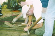 Trever Murawski, wearing a white cap, and Toby Blake scrape away dirt at the site of a prehistoric house near Tonganoxie.