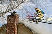 Tonganoxie volunteer firefighters force water on a home during a training exercise last Saturday. The house was heavily damaged in the May 11 tornado, and the owner agreed firefighters could burn it down so they could practice search-and-rescue measures.
