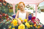 Hillary Chauvin arranges a bouquet of yellow roses in her grandmother's floral booth during Saturday's Tonganoxie Days festivities. Booths lined three blocks of Fourth Street, and activities also were going on at the VFW Memorial Park, the Leavenworth County Fairgrounds, Tonganoxie Elementary School, the Tonganoxie City Library and the Amanna elan bed and breakfast. Hillary and her mother watched the booth for Hillary's grandmother.