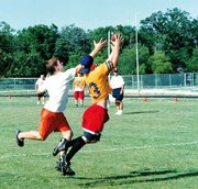 Aaron Swallow, McLouth, catches the football as a player from Piper comes in close. In the background are, from left, Don Elston, Tonganoxie, Jeff Holland, McLouth, and Dick Tatro, coach for Piper.