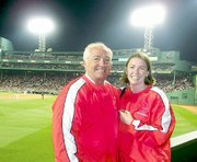 Andy and Amanda, wearing their Tonganoxie baseball attire, stand near their right-field seats at Fenway Park.