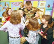 Exuberant students in Pam Fields' third-grade class rushed to greet Jeremy Goebel Monday morning when he visited Tonganoxie Elementary School. Students pictured clockwise from far left are, Emily Minear, Sarah Smith, Chantel Sample, Sierra Baber, Madison Cunningham, Kylee Wilson and Leah Cugno. Pictured in the background is Goebel's wife, Lisa. Goebel is the school's physical education teacher who was called into active duty earlier this year. He is expected to return to Tonganoxie and resume his teaching position in late January.