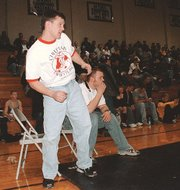 THS wrestling coach Jeremy Goebel uses body language while watching a wrestler compete.