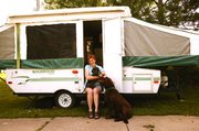 Shellie Hardisty holds her dog, Dottie, as she sits in the doorway of her popup camper. Hardisty, Dottie, and her other dog, Cocoa, visited Hardisty's family in Tonganoxie during the Fourth of July weekend, before heading back to continue her year-long tour.