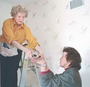 Patti Pietras hands a roll of damp wallpaper to her mother, Helen Terry, as they finish applying wallpaper to the bathroom of a new home in Springdale.