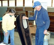 Susy Ross and Del Englen try to decide how to display an antique child's coffin. The unused coffin and other mortuary antiques, which were donated by Quisenberry Funeral Chapel, will be displayed together.