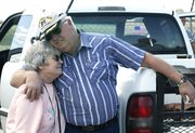 Margarete and Marvin Harrison share a hug after watching the landing of Virgin Atlantic GlobalFlyer.