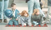 These three children brought along a comfortable blanket to sit on while watching the parade.