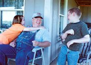 Lenny Lawson joked with two of his grandchildren at his 58th birthday party held on the front porch of his rural Tonganoxie home in May. Lawson died on Sunday in a helicopter accident in Missouri.