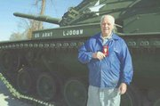 Bill Lux stands before an army tank at VFW Memorial Park as he holds his Korean medal.