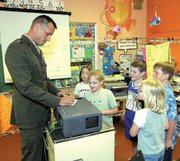 Capt. Chris Phelps of the U.S. Marine Corps autographs a piece of paper for Christopher Tiner on Monday morning. Also pictured, from left clockwise, are Sarah Rahjes, Seth Ahart, Jonathan Hendrix and Baylie Kiefer.