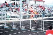 Kyler Madeira stretches over a hurdle during the Tonganoxie Invitational on May 6. Teams braved a cold, rainy evening as Tonganoxie won the girls team title and Lansing clinched the boys crown.