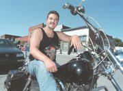 Chris McDaniel, who graduated from Tonganoxie High School in 1996, sits on his Harley-Davidson motorcycle parked on Fourth Street. McDaniel, who is in the U.S. Navy, says he's used much of what he learned at Tonganoxie High School during his career.