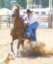Courtenay DeHoff holds onto Nick during a rodeo last summer.