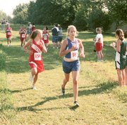 Christy Weller checks on her opponents as she chases Kansas City Christian's Courtney Ford. Weller won the race with a time of 13 minutes, 18 seconds. She finished four seconds ahead of Ford as the THS girls won the team title.