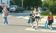 Tyler Hammond, left, and Sean Hammond, far right, cross the street beside Tonganoxie Elementary School on Tuesday morning at the start of the first day of school. Accompanying the boys are their mother, Cheryl Macek, and sister, Madison Macek. School crossing guard Helen McBroom holds a stop sign.
