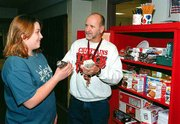 Running his shop before school, Bill Shaw sells a package of doughnuts to Savanah Stufflebean. He also sells other breakfast snacks, as well as notebooks, pencils and pens. After school, Shaw moves his shop to the front of the school where students can buy after-school snacks. The proceeds from the portable store are used to purchase equipment for the junior high media class.
