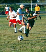 Chris Laurent and Brad Bray pursue a Basehor-Linwood player in last Thursday's game at Chieftain Park. THS won in overtime 1-0.