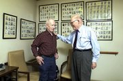 """Walter Denholm, 76, left, says he's been """"doctoring"""" with Phil Stevens """"since right after he came to Tongie,"""" and considers Dr. Phil a good friend as well as a physician. """"You bet,"""" said Denholm, """"and if he doesn't know he'll send you to of docs won't do that."""" The photos on the wall are of babies Dr. Stevens delivered during his first eight years of practice."""